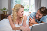 Cute couple relaxing on bed using the laptop