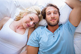 Cute couple relaxing on bed smiling at camera