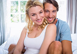 Cute young couple relaxing on bed smiling at camera