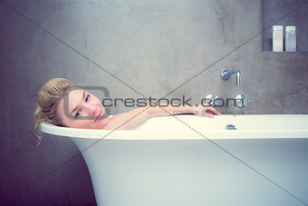 Serene blonde lying in the bath smiling at camera