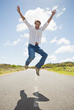 Handsome casual man leaping on a road smiling at camera