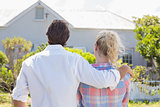 Cute couple standing together in their garden looking at house