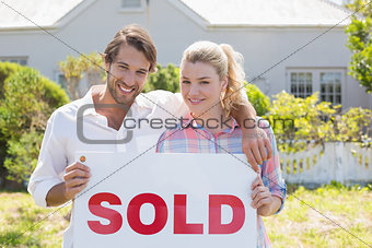 Cute couple standing together in their garden holding sold sign