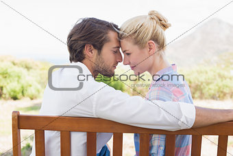 Cute couple sitting on bench together smiling at each other