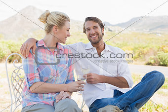 Cute couple sitting in the garden enjoying wine together