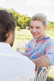 Happy young couple sitting in the garden enjoying wine together