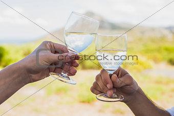 Couple clinking wine glasses outside