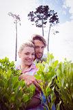 Smiling couple embracing outside among the bushes