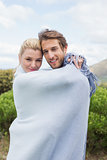 Cute smiling couple standing outside wrapped in blanket