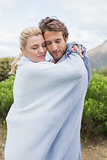 Cute affectionate couple standing outside wrapped in blanket