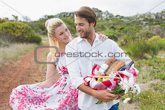 Cute couple going for a picnic smiling at each other