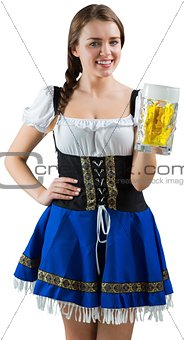 Pretty oktoberfest girl smiling at camera holding beer