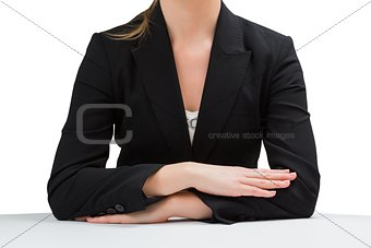 Businesswoman sitting at desk with arms crossed