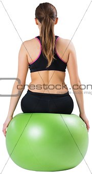 Fit brunette sitting on exercise ball