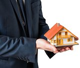 Businessman holding miniature house model