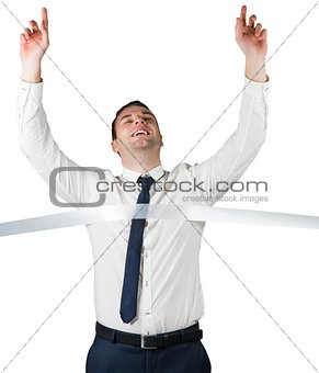 Smiling businessman crossing finishing line