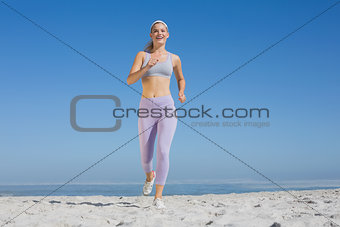 Sporty blonde on the beach jogging towards camera