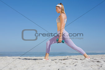 Sporty blonde doing weighted lunges on the beach