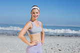 Sporty smiling blonde standing on the beach