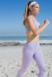 Sporty focused blonde jogging on the beach