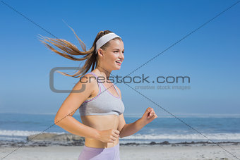 Sporty smiling blonde jogging on the beach