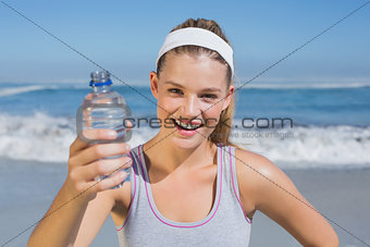 Sporty smiling blonde showing water bottle on the beach