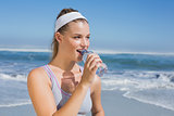 Sporty smiling blonde drinking water on the beach