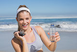 Sporty happy blonde standing on the beach with bottle and skipping rope