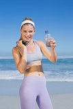 Sporty happy blonde standing on the beach with water bottle and skipping rope