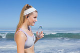 Sporty blonde on the beach drinking water