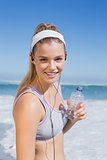 Sporty blonde on the beach smiling at camera with water bottle