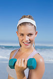 Sporty happy blonde lifting dumbbell on the beach