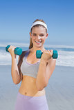 Sporty happy blonde lifting dumbbells on the beach
