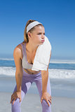 Sporty blonde standing on the beach with towel