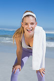 Sporty smiling blonde standing on the beach with towel