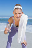 Sporty smiling blonde standing on the beach with towel and bottle