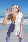 Sporty tired blonde drinking water on the beach