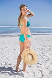 Pretty smiling woman in bikini on beach holding sunhat