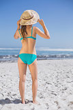 Slender woman in bikini on beach wearing sunhat