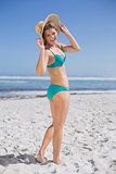 Slender woman in bikini on beach wearing sunhat smiling at camera