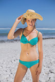 Pretty smiling woman in bikini on beach wearing sunhat