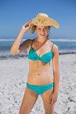 Pretty smiling woman in bikini on beach wearing sunhat