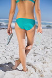 Rear view of fit woman in bikini on beach holding flip flops