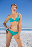 Fit woman in bikini on beach smiling