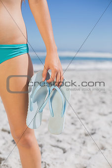 Mid section of fit woman in bikini on beach holding flip flops