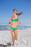 Fit woman in bikini jogging and smiling