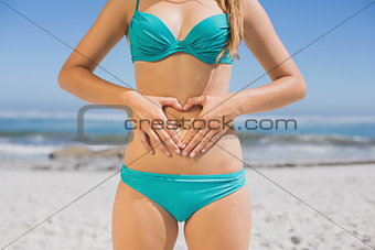 Fit woman in bikini on the beach making heart shape on stomach