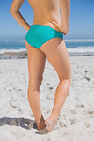 Lower half of fit woman standing on beach