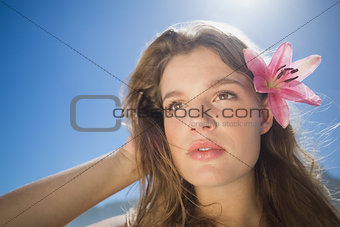 Beautiful blonde with flower hair accessory on the beach