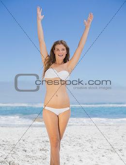 Beautiful happy blonde on the beach in white bikini